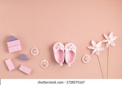 Cute newborn baby girl shoes with festive decoration over pink background. Baby shower, birthday, invitation or greeting card idea