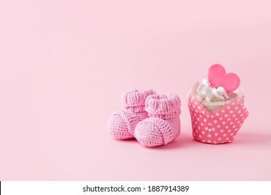 Cute newborn baby girl shoes with festive decoration cupcake over pink background. Baby shower, birthday, invitation or greeting card idea, copy space, flyer, invitation, monochrome concept