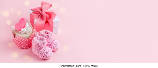 Cute newborn baby girl shoes with festive decoration cupcake and gift box  over pink background. Baby shower, birthday, invitation or greeting card idea, copy space, flyer, invitation, monochrome