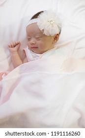 Cute newborn baby girl sleeping in bed.