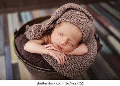 Cute newborn baby in the hat. Sleeping baby on a dark background. Closeup portrait of newborn baby. Baby goods packing template. Nursery. Medical and healthy concept.