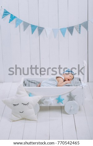 cute newborn baby in hat sleeping in wooden baby cot with star pillow near  by 5cdd8524365c