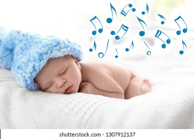 Cute newborn baby in knitted hat sleeping on bed and flying music notes. Lullaby song