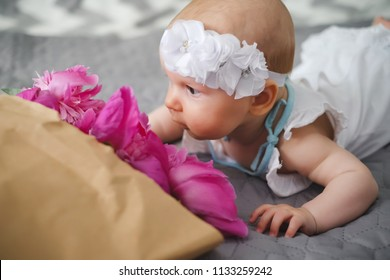 Cute newborn baby lying on the bed and playing with ping bouquet of pion flowers