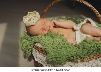 Cute newborn baby is  sleeping in a crown  in a basket.  Have a nice dreams baby.