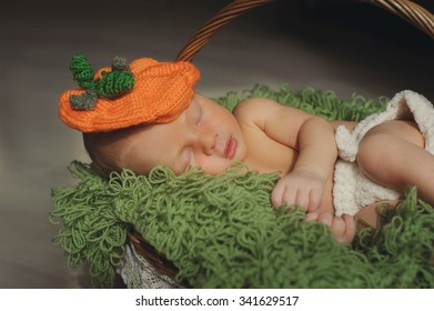 Cute newborn baby is  sleeping in a hat   in a basket.  Have a nice dreams baby.