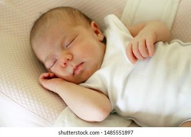 Cute newborn baby is sleeping on her bed.