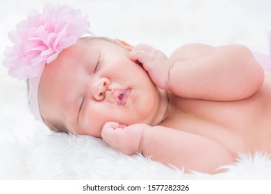 Cute newborn baby wears a pink flower crown lies swaddled in a white blanket. Close-up view.