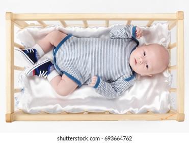 cute newborn baby in wooden bed