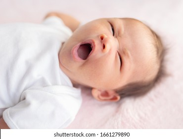Cute newborn baby yawning before sleepon the bed. Portrait
