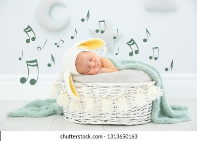 Cute newborn child wearing bunny ears hat sleeping in baby nest and flying music notes indoors. Lullaby song