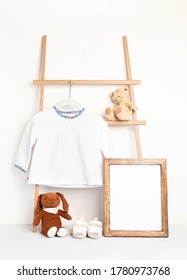 Cute newborn clothes hanging on the rack. Organic cotton baby apparel mockup.