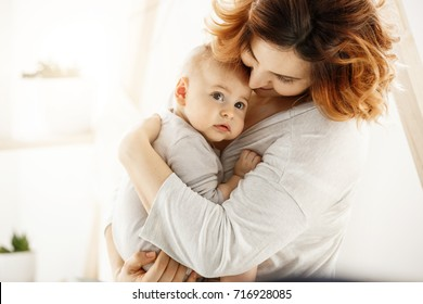 Cute newborn kid frightenedly looks aside while good-looking young mother gently huggs baby expressing her love and support. Family concept.