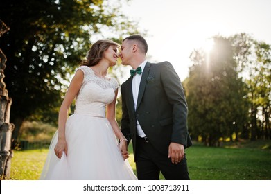 Cute newly married couple kissing next to an old fountain on their wedding day.