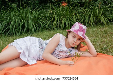 Cute offended Caucasian little girl, close-up outdoor portrait