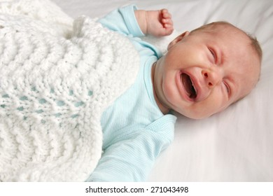 A cute one month old newborn baby is laying on her back in the crib 863bfc041caa