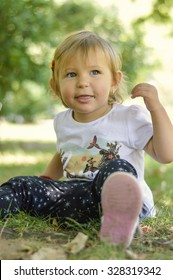 Cute one year old baby girl sitting on grass in a park