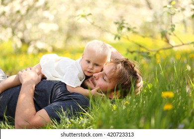 A cute one year old baby girl is hugging her young father as they relax in a flowering apple tree orchard on a spring day.