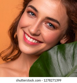 Cute ordinary young woman posing with monstera tropical leafs. Fresh clean skin with flawless texture. Skin care beauty cosmetology concept. Space for text