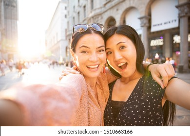 Cute outdoor portrait of funny pretty best friends asian girls having fun making selfie at city center, positive crazy emotions, traveling together in milan, italy, Europe