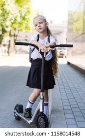 cute pensive schoolchild with backpack riding scooter and looking away on street