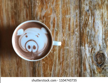 Cute pig face latte art coffee in white cup on wooden table ; cute latte art in your cup , love eat love coffee