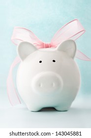Cute piggy bank with pink bow and ribbon. Front view