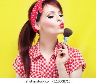 Cute pin up girl applying blusher