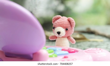 Cute pink crocheted bear doll playing a toy notebook in the garden in beautiful morning, implying fast learning of technology of children today