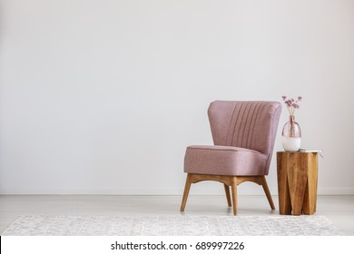 Cute pink flowers in glass vase placed on wooden table standing by small chair