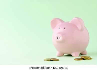 Cute pink piggy bank on a green background with loose coins and copy space conceptual of savings, investment, banking, business and finances
