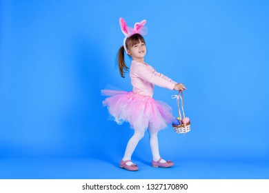 Cute pink young girl child daughter wears pink dress like rabbit playing in easter holiday game with rabbit ears and ester eggs on isolated blue background. Spring is coming and Easter holiday concept