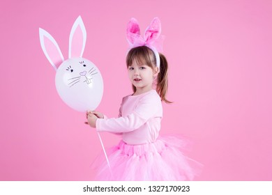 Cute pink young girl child daughter wears pink dress like rabbit playing with rabbit balloon with rabbit ears on isolated pink background. Spring is coming and Easter holiday concept