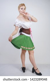 cute plus size girl with a short haircut and big Breasts dressed in a national Bavarian dress on a white background in the Studio. sexy curvy caucasian woman standing in cite dress with green skirt.