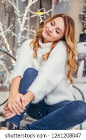 Cute plus size woman near house, that covered in garlands and christmas decorations. She wears white cozy sweater. Space for text