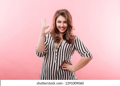 Cute plus size woman in stripe blouse smiling and looking at camera while standing on pink background and showing OK gesture