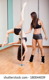 Cute pole fitness instructor helping a student with her technique
