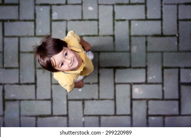Cute portrait of little boy, standing on the street, looking up, shot from above