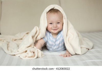 Cute portrait of smiling baby boy lying on bed under white blanket