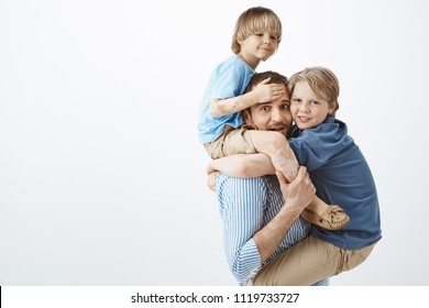 Cute positive family feeling great while playing together in park. Portrait of happy good-looking single father holding son with vitiligo on shoulders and older sibling on chest, fooling around