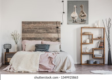 Cute poster with two ducks on white wall of tasteful bedroom interior with bed with pastel pink bedding