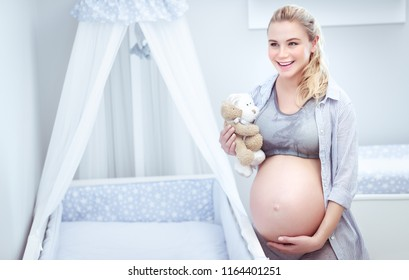Cute pregnant woman at home, the future mother with tenderness touches her tummy, enjoys preparing a children's room for her child, happy maternity concept
