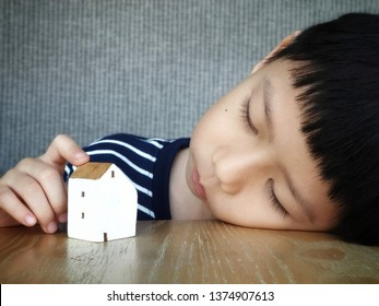 A cute preschool asian boy lay his head on the table mind blowing looking at a toy wooden house feeling lonely. relocation, loneliness, homesick concept - close up