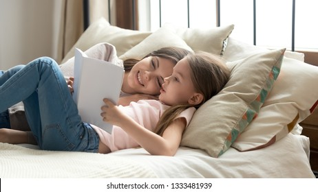 Cute preschool child daughter holding book reading fairy tale to mom lying in bed together, happy mother listening focused little kid girl learning to read relaxing in bedroom enjoy bedtime stories