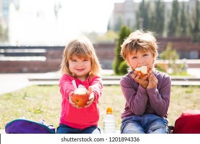 Cute preschool children eating apples outdoors. childhood, healthy school breakfast concept.