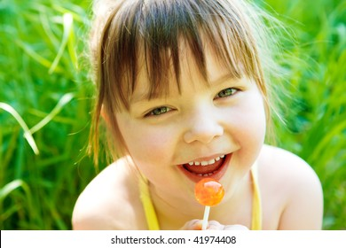 Cute preschool girl with lollipop, in park