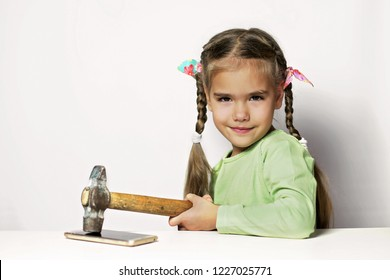 Cute preschool girl looking mischievously, holding a hammer and going to destroy a mobile phone, digital device addiction, childhood and education