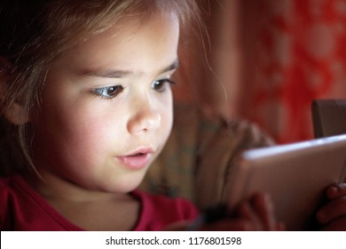 Cute preschool girl looking movie with the smart phone, digital device addiction, childhood and education