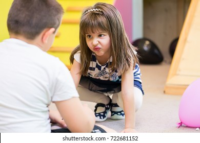 Cute pre-school girl making a funny face while looking at a boy with hostility during playtime at the kindergarten