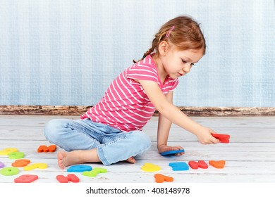 Cute preschool girl playing with letters